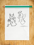 Angel and Devil. Doodle drawing of angel and devil on white paper as concept of conscience and moral dilemma in fight of good and evil Royalty Free Stock Photography