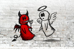 Angel and devil fighting; doodle drawing on white brick wall. Doodle drawing of angel and devil fighting on white brick wall. Concept of conscience; decisions Royalty Free Stock Images