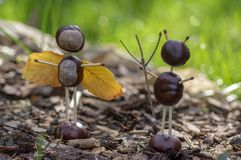 Angel and devil figures made from chestnuts and safety matches and dry leaves in the garden. Angel and devil figures made from chestnuts and safety matches and stock photography