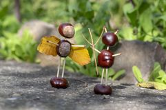 Angel and devil figures made from chestnuts and safety matches and dry leaves in the garden. Angel and devil figures made from chestnuts and safety matches and royalty free stock photography