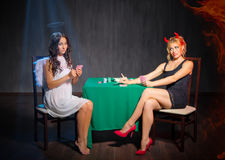 Angel and devil playing cards at room Royalty Free Stock Photos