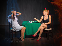 Angel and devil playing cards Stock Photography