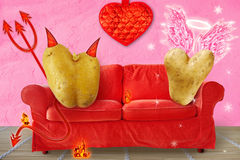 Angel and Devil. Two heart shaped potatoes on a couch. One of them is the devil with tail and pitchfork. The other potato is an angel with wings and aureola Royalty Free Stock Photos