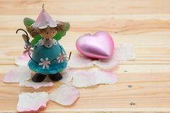 Angel doll with petal and pink heart, Valentine. Decoration of mini angel doll standing on pink petals and near pink heart on brown textured wooden background Royalty Free Stock Photography