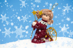 Angel doll on snowdrift with snowflake Royalty Free Stock Photography