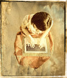 Angel emailing. A woman sitting against a background of clouds, as if it`s an angel typing an email or using the laptop. Vintage effect Royalty Free Stock Photo