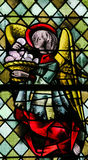 Angel with a Eucharist. On a stained glass in the cathedral of Rouen, France stock image