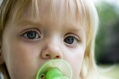 Angel Eyes. Slightly grainy image of a little girl with a pacifier with extreme narrow focus on her left eye royalty free stock image