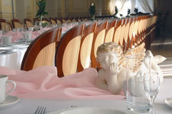 Angel figure & pink table. An Angel figure on pink banquet table stock photography