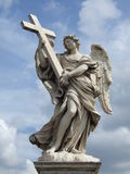 Angel figure with a stone cross Royalty Free Stock Images