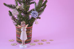 Angel figurine and fir branches on pink Stock Photos