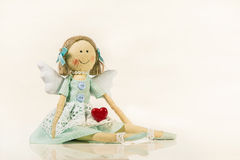 Angel figurine holding a red heart in his hands - isolated objec Stock Image