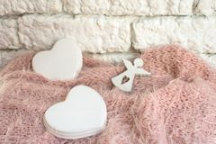 Angel figurine with a porcelain heart on a pink blanket on a light wall. Love royalty free stock photo