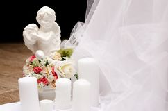 Angel figurine with wedding candles and roses royalty free stock images