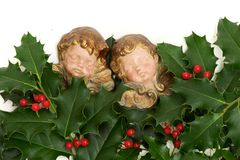 Angel figurines with green holly leaves and red berries Royalty Free Stock Photos