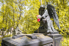 Angel with flowers on the grave. Angel with flowers at the cemetery. The gravestone in the old cemetery in St. Petersburg. The monument, a sculpture in the Royalty Free Stock Photos