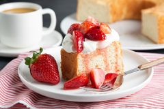 Angel food cake with whipped cream and strawberries. Portion of angel food cake served with whipped cream and strawberries royalty free stock photo