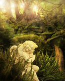 Angel in garden. Classical cherub angel in mystical garden setting with rays of light streaming above Royalty Free Stock Images