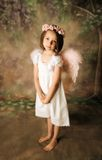 Angel Girl. Beautiful young girl wearing angel wings and flower halo with somber expression Stock Photography