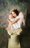 Angel Girl. Beautiful young girl wearing pink angel wings and flower halo sitting on a pedestal Stock Photos