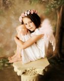 Angel Girl. Beautiful young girl wearing angel wings and floral halo Royalty Free Stock Image