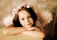 Angel Girl. Beautiful young girl wearing angel wings and floral halo Royalty Free Stock Images
