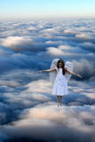 Angel girl above the clouds. Dream of teenage girl, she hovers like an angel over the clouds Royalty Free Stock Photo