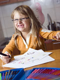 Angel girl with attitude. Portrait of a young girl, wearing angel wings and eyeglasses making funny toothless smile while drawing her artwork with colorful Stock Images