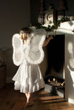 Angel girl before fire place touchting noel Royalty Free Stock Photo
