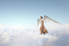 Angel girl flying high. Attractive woman with angel wings on sky background stock photo