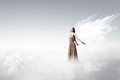 Angel girl flying high. Attractive woman with angel wings on sky background royalty free stock photography