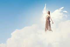 Angel girl flying high. Attractive woman with angel wings on sky background stock image