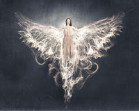 Angel girl flying high. Attractive woman with angel wings on sky background royalty free stock photo