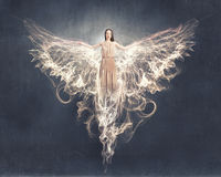 Angel girl flying high. Attractive woman with angel wings on sky background stock photography