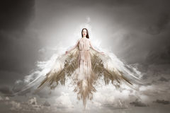 Angel girl flying high. Attractive woman with angel wings on sky background stock photos