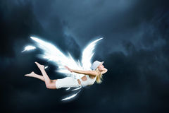 Angel girl flying high. Cute girl with angel drawn wings on dark sky background stock photos