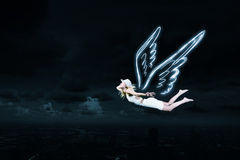 Angel girl flying high. Cute girl with angel drawn wings on dark sky background stock photo