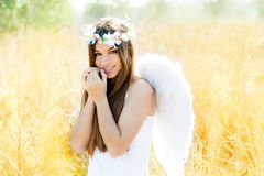 Angel girl in golden field with white wings Royalty Free Stock Photo