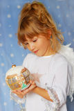 Angel girl holding christmas ball in hand Stock Photo