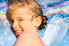 Angel girl with rainbow. A little girl with angel wings and sparkly rainbow background Stock Photography