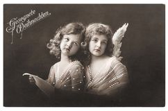Angel girls white wings Christmas greetings card. Angel girls with white wings. Christmas greetings card. Vintage picture with original film grain and blur, 1912 Stock Photo