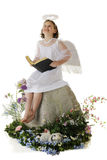Angel Giving Glory. A joyful elemantary angel looking heavenward as she holds a Bible on a rock surrounded by spring flowers.  On a white background Stock Photo