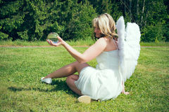 Angel with glass ball II. A young woman as an angel holds a glass ball in hand royalty free stock image