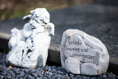 Angel on grave. An angel on a grave with a stone that says: Geliebt beweint und unvergessen Royalty Free Stock Images