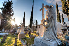 The angel among the graves of the cemetery, facing the sun. A marble angel with his hand on the cross, facing the sun, among the graves of the cemetery, in stock photos
