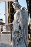 The angel among the graves of the cemetery. A marble angel with his hand on the cross, among the graves of the cemetery, in concentration, holding a wreath royalty free stock photo
