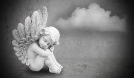 Angel on gray background. Dreamy angel sitting on a gray cloud background Stock Photo