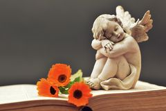 Angel guardian and flowers on the book. Angel guardian and flowers on the old book Stock Photo