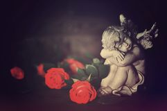 Angel guardian and roses. On dark background stock image
