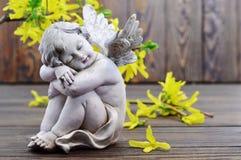 Angel guardian sleeping and spring flowers. Angel guardian sleeping and yellow spring flowers stock photo